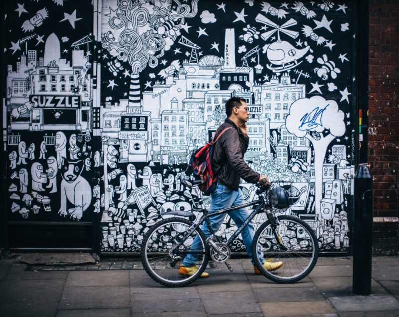 Man walking in front of a graffitied wall with a bike