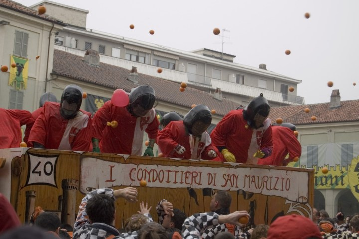 People in their battle wear throwing oranges in Italy at the Battle of the Oranges food festival.