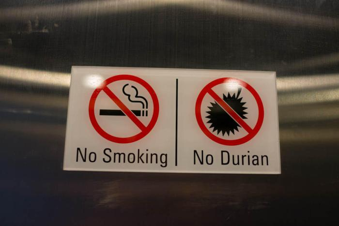 "Two signs on a window, one that says ""no smoking"" and the other "" no durian"" weird laws in Southeast Asia"