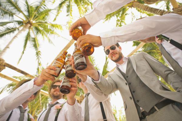 A group of men in suits cheers their bottles of beer
