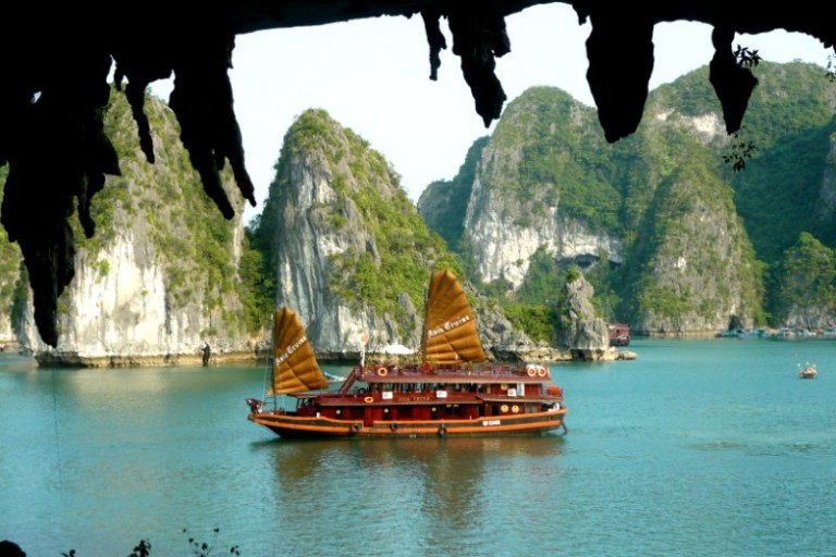 Brightly coloured Vietnamese junk boat cruising past inlets on Halong Bay, Vietnam