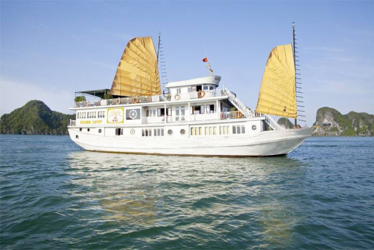 A white boat with yellow sails on Halong Bay