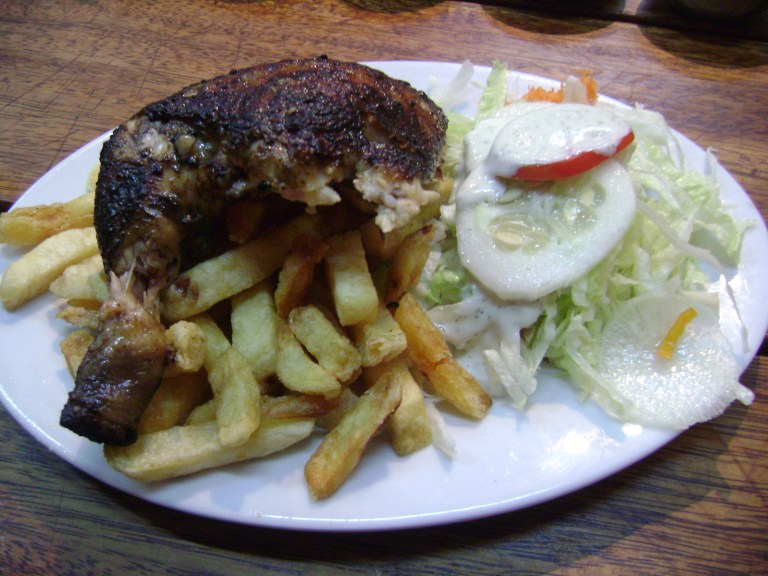 Pollo A La Brasa, chips and salad on a plate
