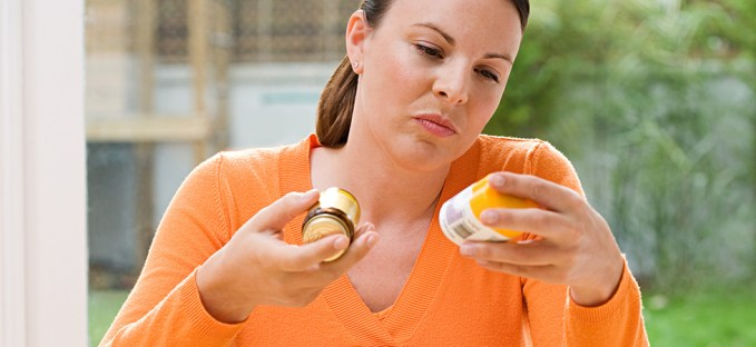 Woman looking at supplement labels wearing an orange sweater