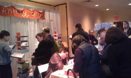 Norah signs books at the Knitty City booth.