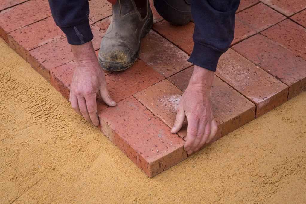 crop faceless construction workman laying bricks