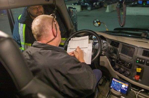 Truck driver filling out paperwork.