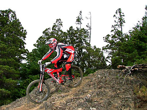 Good braking/downhill technique – Notice the rider is off the saddle with their weight shifted way back – Also note that neither their arms or legs are locked.