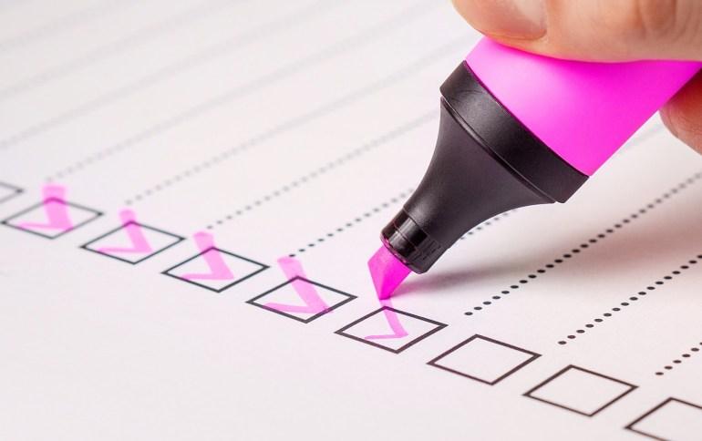 Folha de papel com uma pessoa segurando uma caneta e selecionando os itens da sua pesquisa, a respeito do que é clima organizacional.