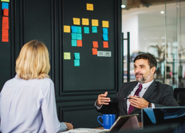 Gestor conversando com integrante da equipe em reunião de avaliação de desempenho