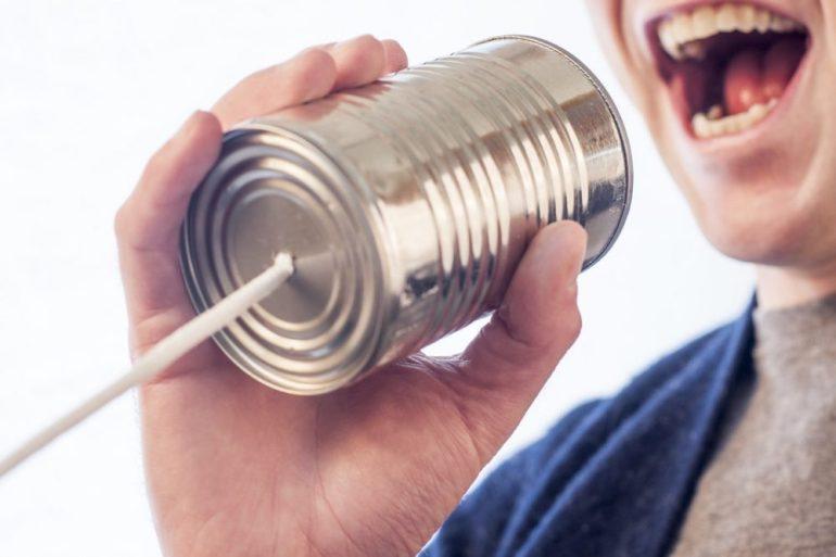 homem se comunicando com a empresa com uma latinha de metal.