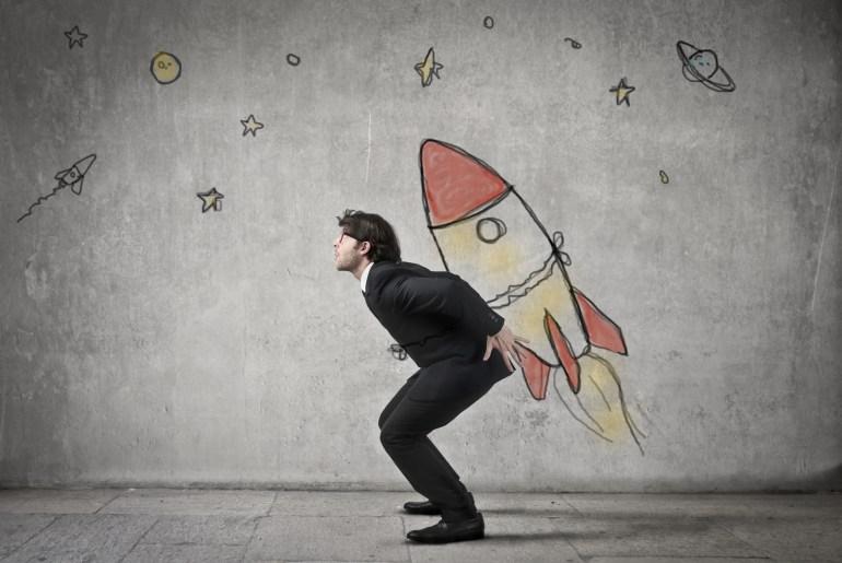 """Empresário com desenho de foguete nas costas, simulando o sucesso da empresa """"decolando"""""""