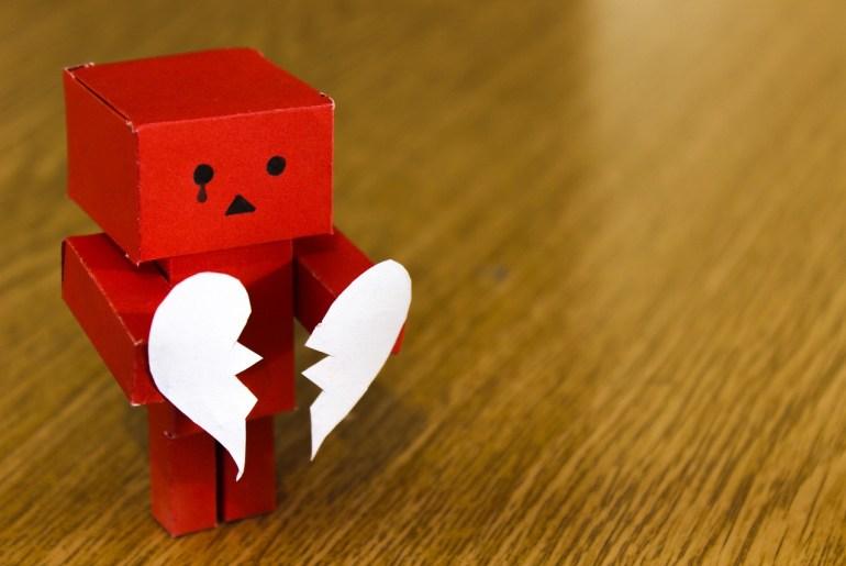 boneco segurando coração partido