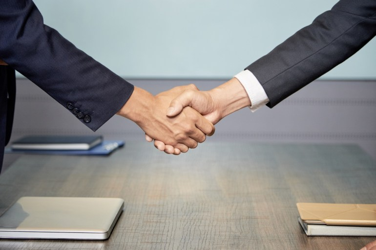 duas pessoas apertando as mãos