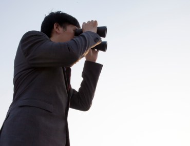 homem observando um alvo com um binóculos