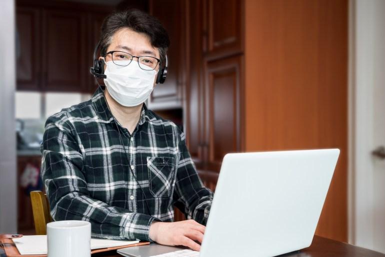Colaborador trabalhando de casa com máscara por causa do coronavírus