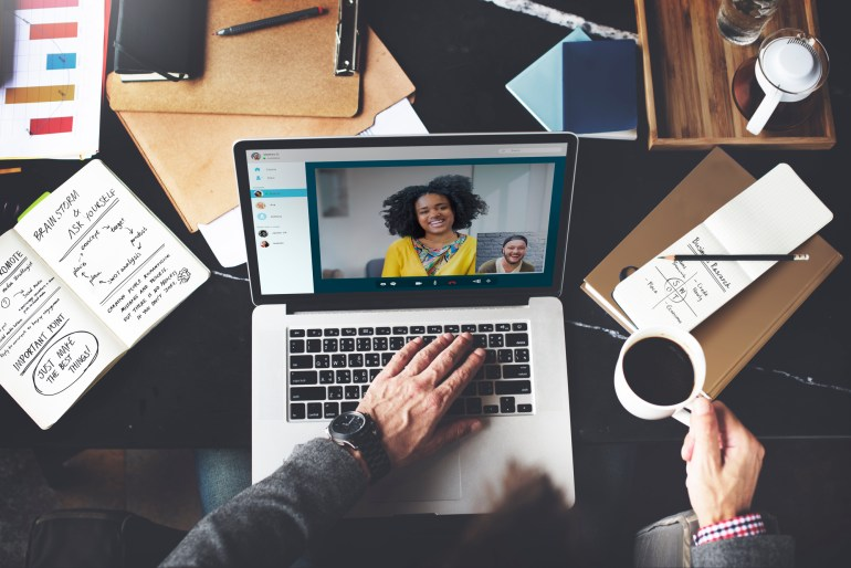 Homem fazendo videochamada no notebook com uma colega