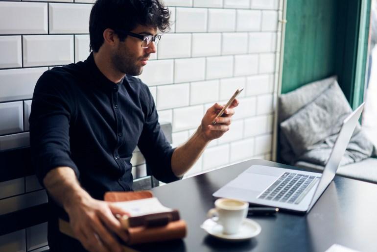 Homem sentado em frente ao computador mexendo no celular