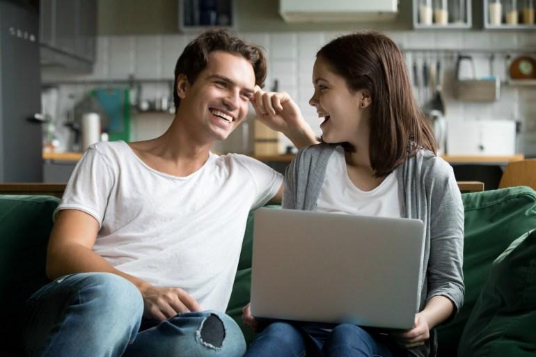 Casal sorridente lendo conteúdo digital no computador.