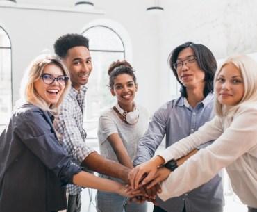 Equipe de trabalho sorridente composta por pessoas diversas.