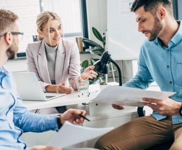 Equipe de trabalho reunida definindo estratégia de gestão de clientes.