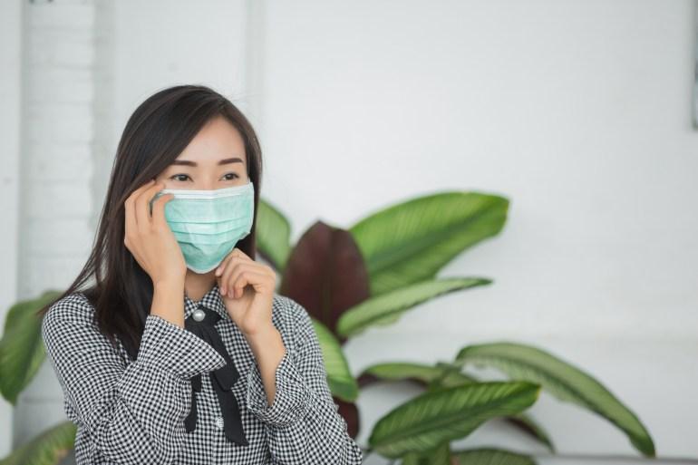 Mulher com máscara facial aguardando atendimento.