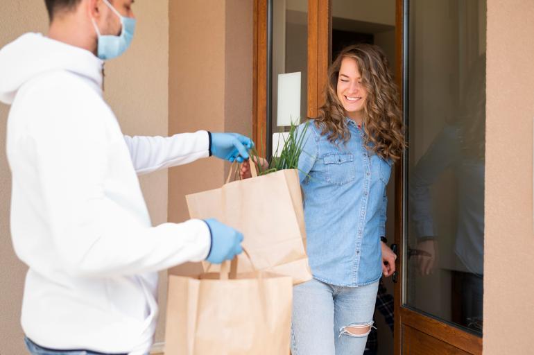 Cliente feliz recebendo os produtos em casa através do serviço de delivery