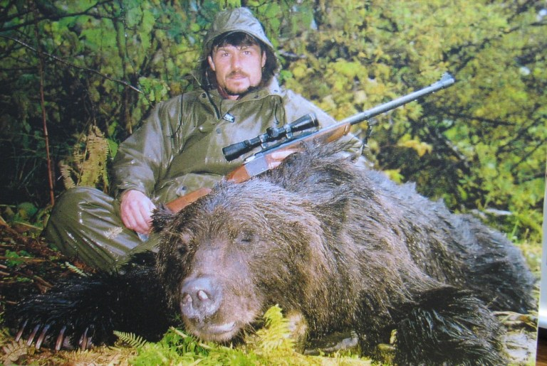 James Reed with rifle and bear