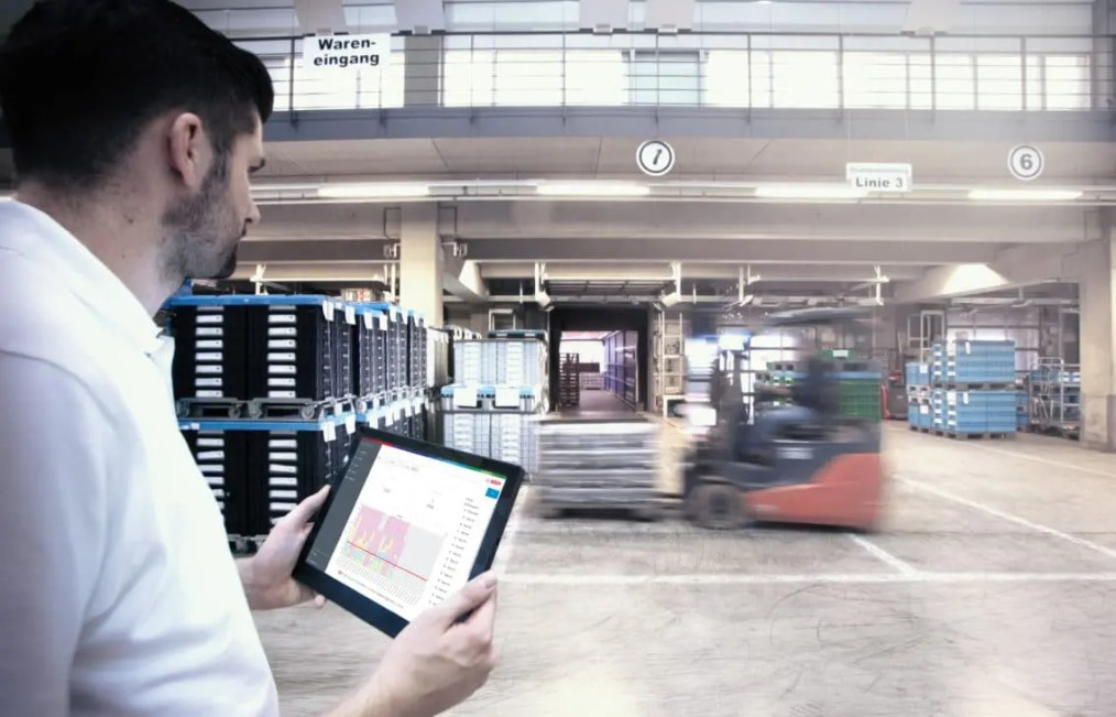 Man holding a tablet computer with a forklift in the background.