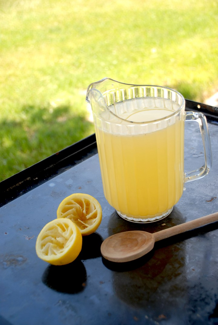 pitcher lemonade, wooden spoon, juiced lemon halves