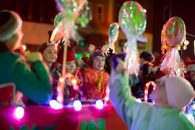 children sitting on lighted and decorated float in Christmas parade in New York