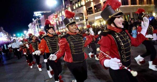 baton twirlers in marching band wearing red and black uniforms in Christmas parade in New York