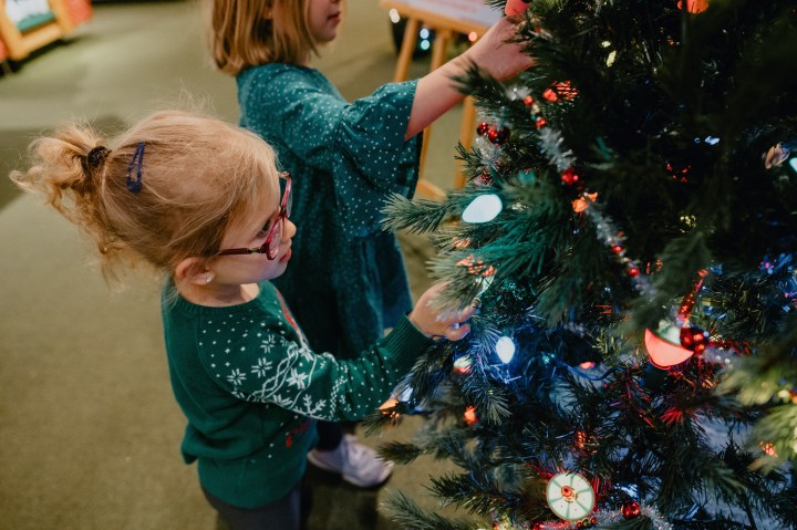 Two young girls stop to admire bubble lights and tinsel garland on vintage Christmas tree at Bronner's.