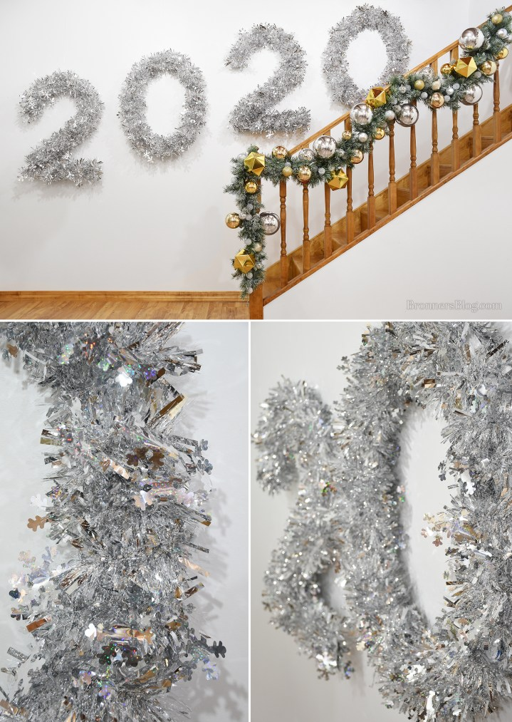 2020 foam-core numbers are wrapped in tinsel garland and hung from the wall along a silver and gold decorated railing.