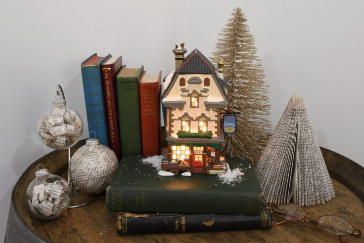 """Russell Street Books,""our Department 56 giveaway, displayed on top of books atop wine barrel with ornaments, trees and eyeglasses"