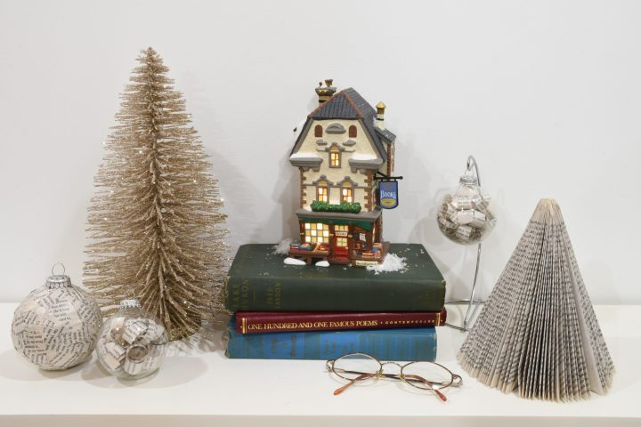 """Russell Street Books,"" our Department 56 giveaway, displayed on fireplace mantel with books and book-themed trees and ornaments"