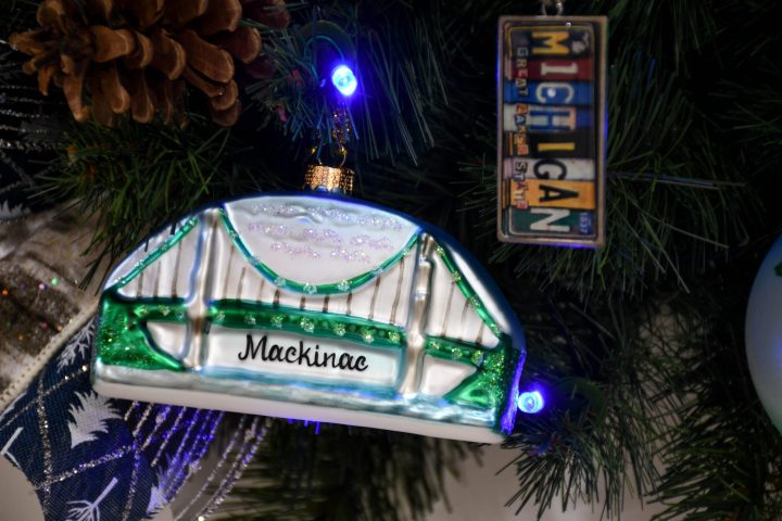 glass Mackinac bridge ornament & acrylic vintage Michigan license plate keychain hanging on a lighted Christmas tree
