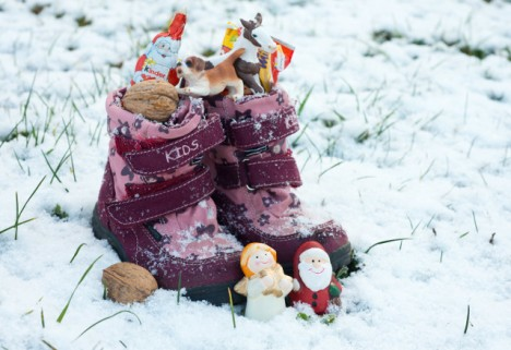 child's pink and purple boots in snowy grass filled with nuts, small toys and treats to celebrate St. Nicholas Day ais how Germany celebrates Christmas