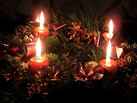 evergreen Advent wreath trimmed with red ribbon and pine cones with all four red candles lit is how Germany celebrates Christmas