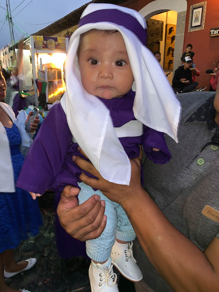 Young baby dressed in traditional wear for the celebration of Semana Santa.