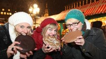 Ladies enjoying large Nuremberg Lebkuchen gingerbread cookies at the Christkindlesmarkt.