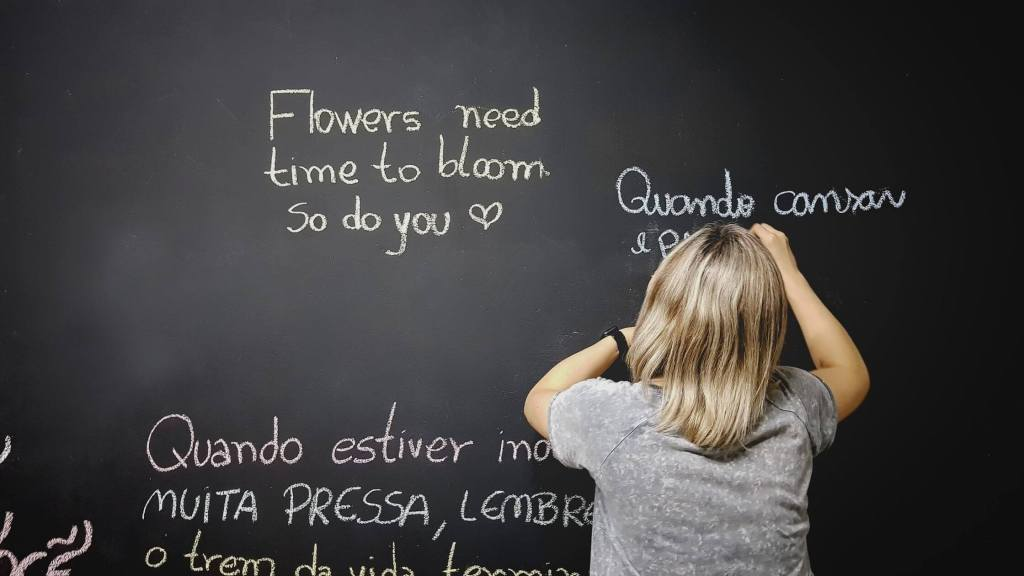 Girl writing sentences in different languages on a blackboard