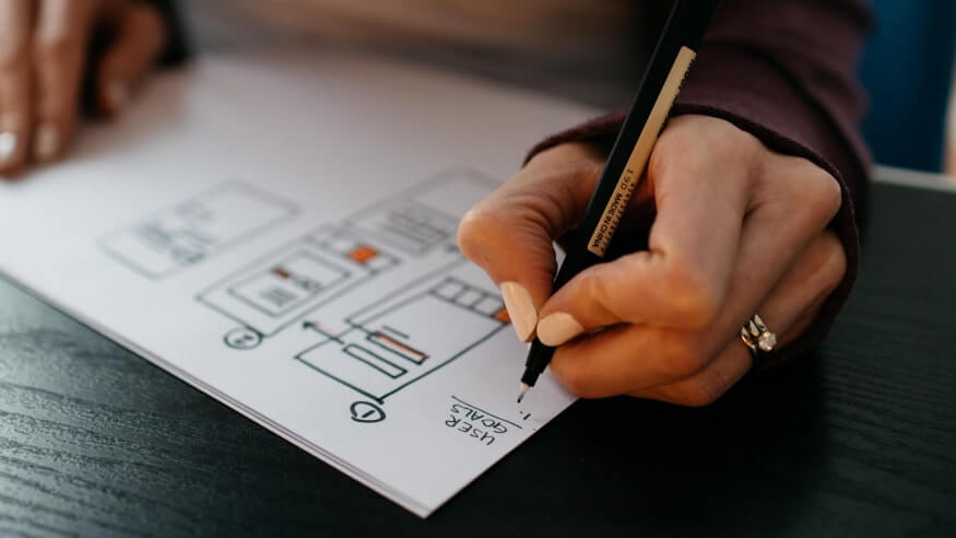 A person drawing interface architecture on paper using pencil