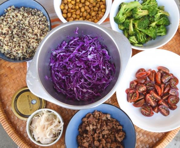 bowls of quinoa, chickpeas, broccoli, tomatoes, cabbage, ground lamb, and sauerkraut