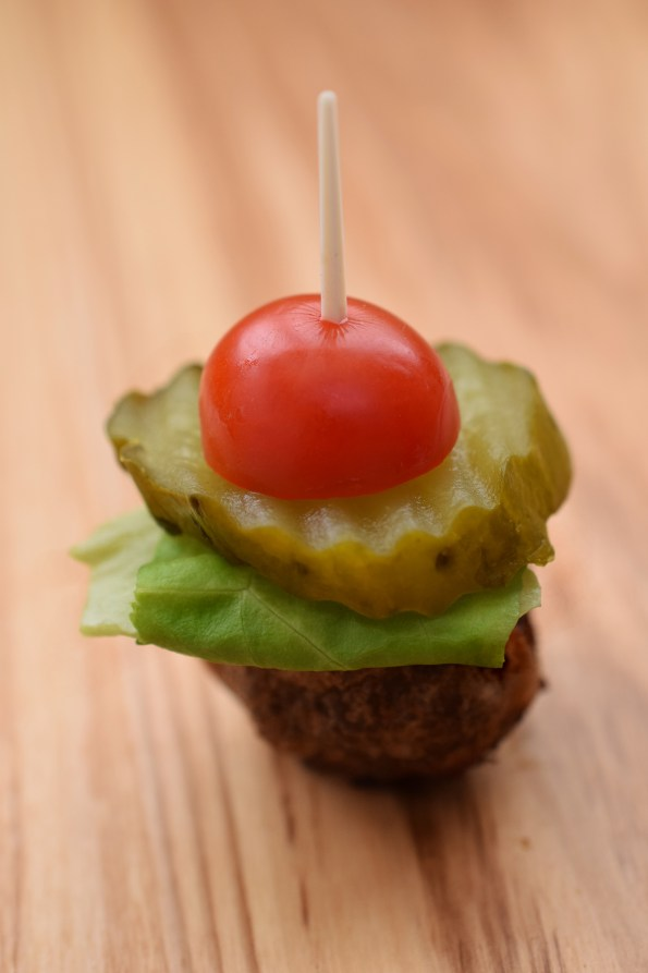 One burger bite. Toothpick through cherry tomato, pickle, lettuce, and hamburger