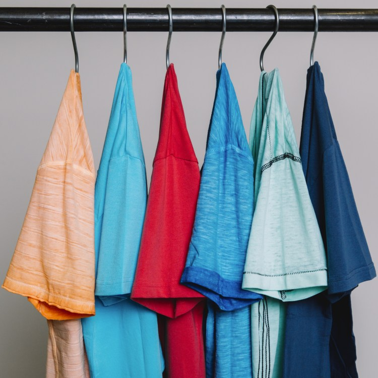 Five men's t-shirts, in colors orange, teal, red, light blue, aqua, and navy blue, hanging up.