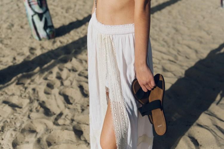 woman wearing white walk-through maxi shirt carrying black and brown sanuk slip-on sandals.