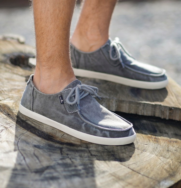 Man wearing grey lace-up Sanuk casual shoes standing on a tree stump.
