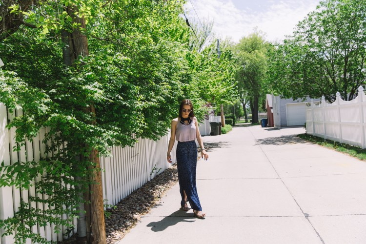 Girl walking through alleyway with white fence on both sides - woman is wearing blush strappy neckline tank with blue and black floral maxi skirt and black swim top styled as a bralette.