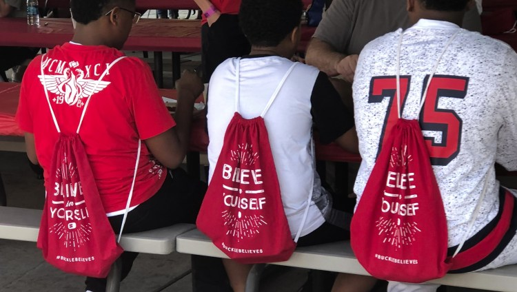 Three mentees sit at picnic table, during TeamMates Graduation Celebration at the Omaha Zoo, while wearing drawstring bags that say to believe in yourself.